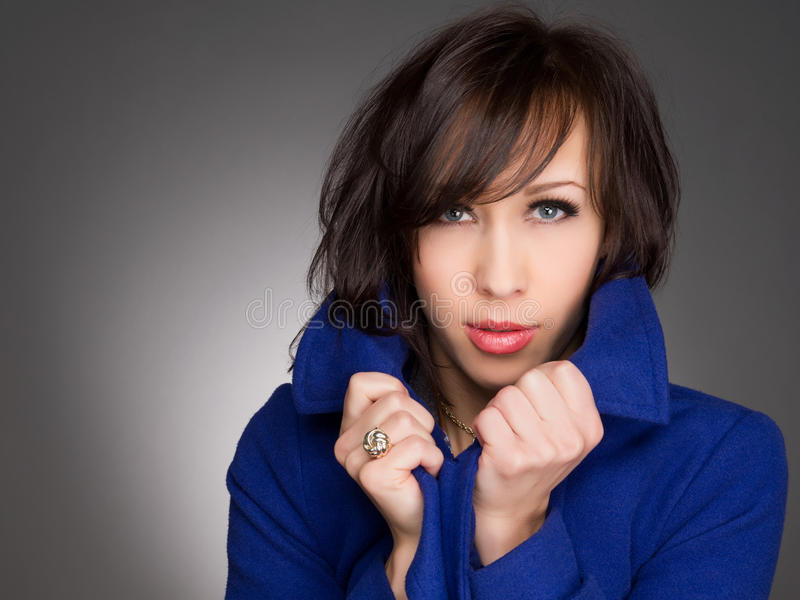 Beautiful young woman deep in thoughts. Wearing dark blue winter coat. Studio portrait. stock images