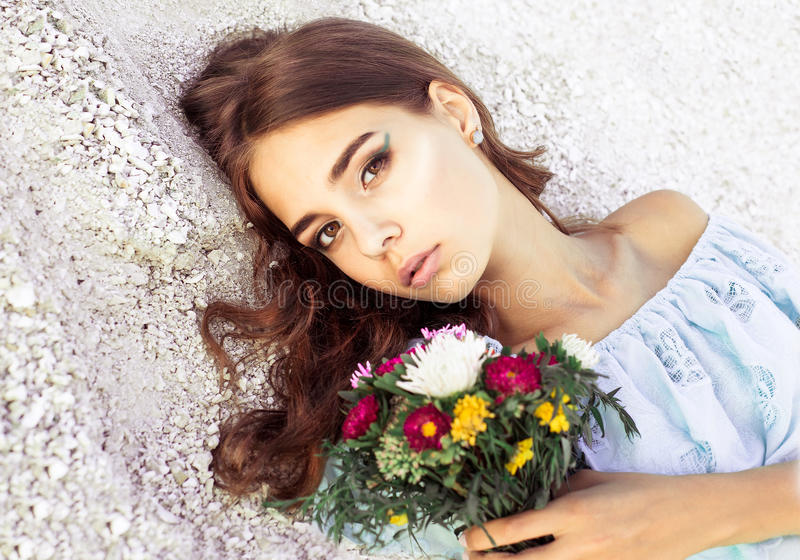 Beautiful young woman with delicate flowers in her hands. Closeup fashionable portrait of girl with elegant makeup. Pretty girl wi stock photos