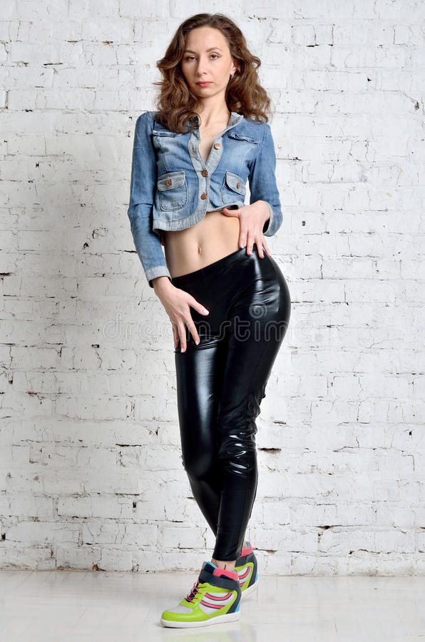 Beautiful young woman in denim jacket and black leather pants. stock photography