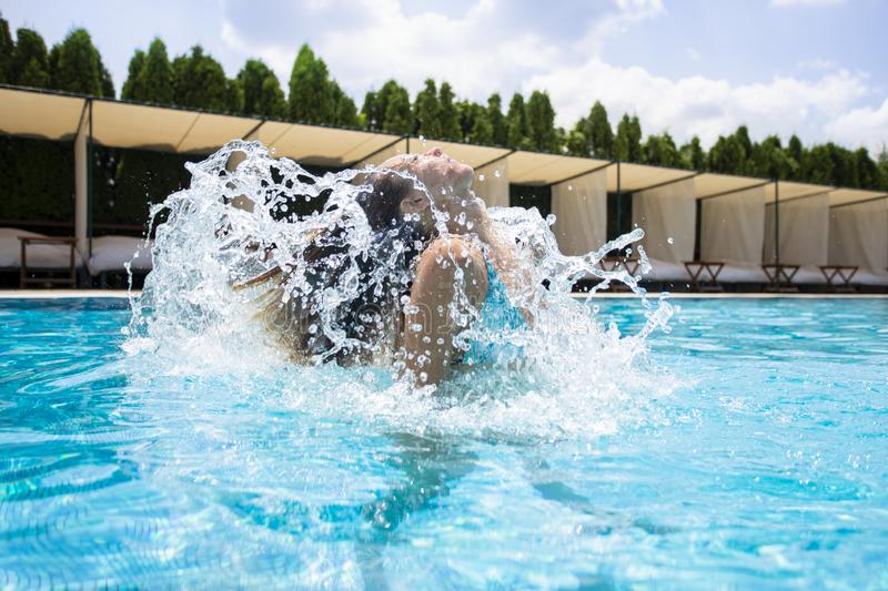 Beautiful young woman diving out of a swimming pool royalty free stock photo