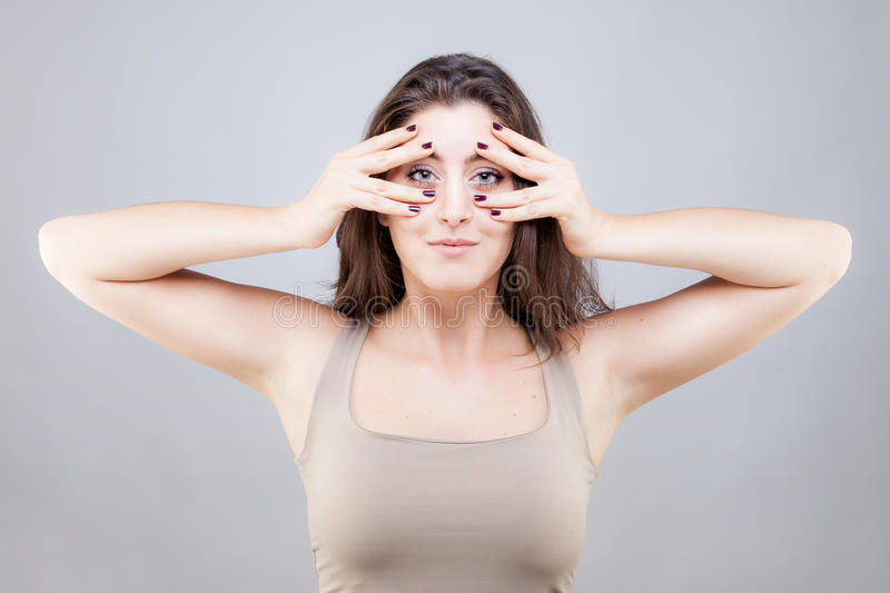 Beautiful young woman doing face yoga pose. Beautiful young caucasian woman doing face yoga pose royalty free stock photo