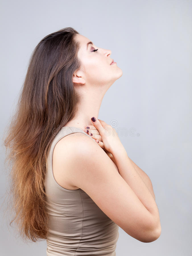 Beautiful young woman doing face yoga pose. Beautiful young caucasian woman doing face yoga pose royalty free stock image
