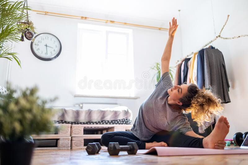 Young woman doing fitness exercise at home royalty free stock photo