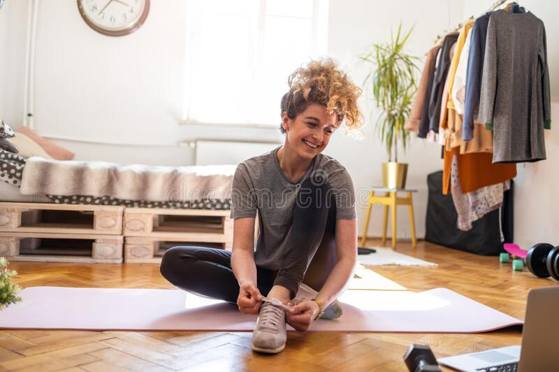 Young woman doing fitness exercise at home stock photo