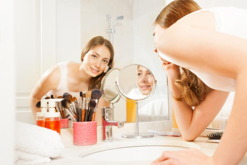 Beautiful young woman doing her makeup in bathroom royalty free stock photos