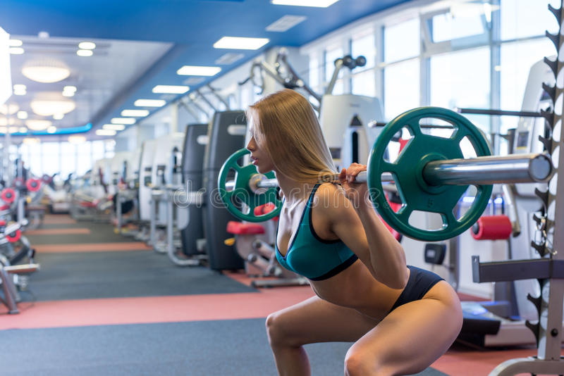 Beautiful young woman doing squats with barbell. In gym royalty free stock photos