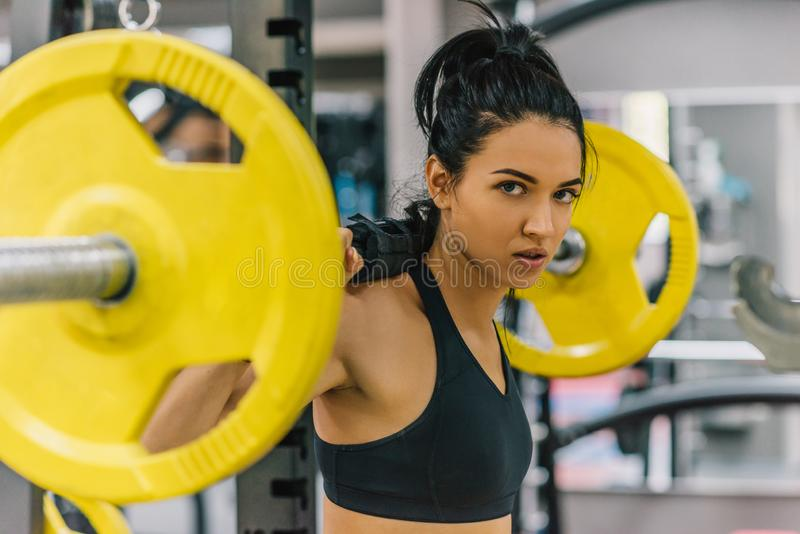 Beautiful young woman doing workout in the gym, pushing yellow barbell on shoulders. Female hard workout for cross fit. People, royalty free stock image