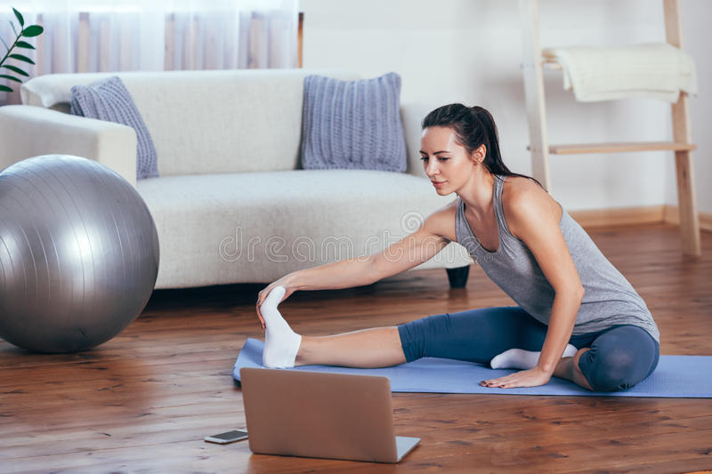 Beautiful young woman doing yoga at home. stock image