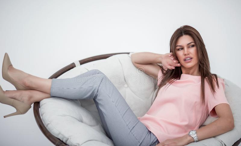 Beautiful young woman dreams of sitting in a comfortable chair royalty free stock photo