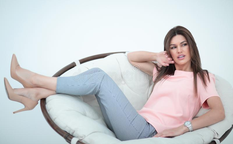Beautiful young woman dreams of sitting in a comfortable chair stock photos
