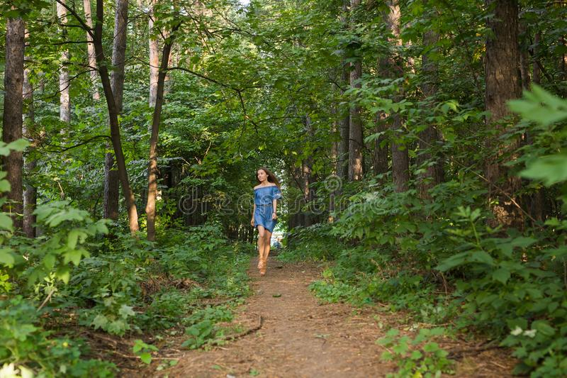 Beautiful young woman in dress runing in the summer forest. Beautiful woman in dress runing in the summer forest stock photography