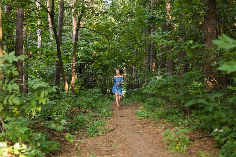 Beautiful young woman in dress runing in the summer forest. Beautiful woman in dress runing in the summer forest royalty free stock image