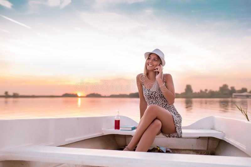 Beautiful young woman in a dress sitting on the boat and talking with her boyfriend on mobile phone in a sunset stock photo