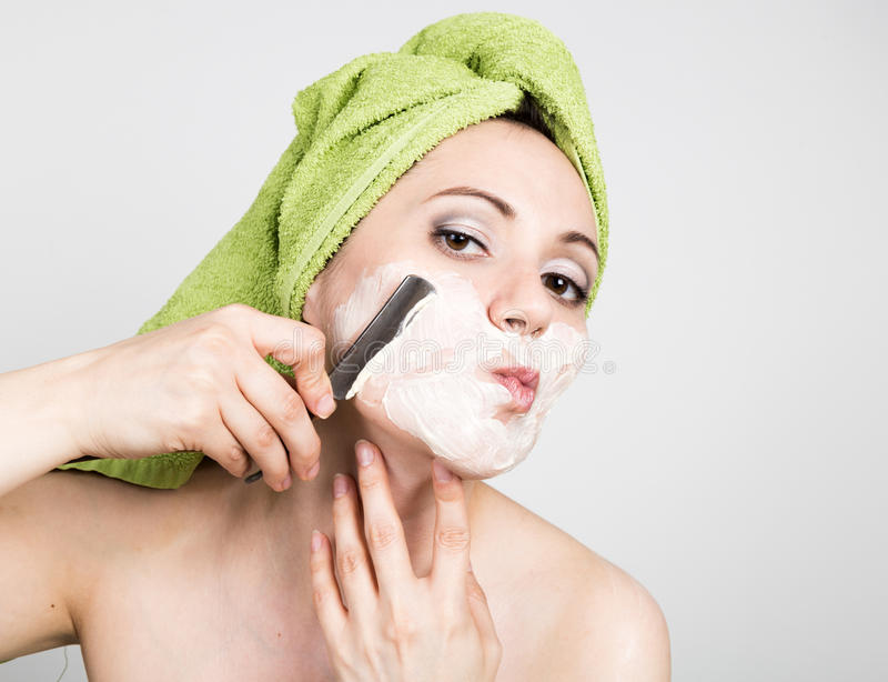 Beautiful Young woman dressed in a bath towel shaves with a straight razor. beauty industry and home skin care concept royalty free stock photography