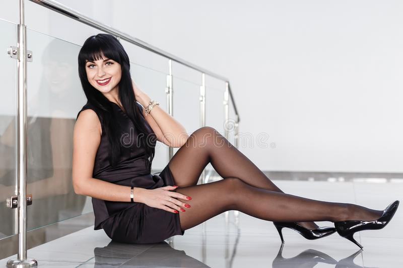 Beautiful young woman dressed in a black business suit with a short skirt is sitting on a floor in a white office. Smiling,. Beautiful young woman dressed in a stock photo