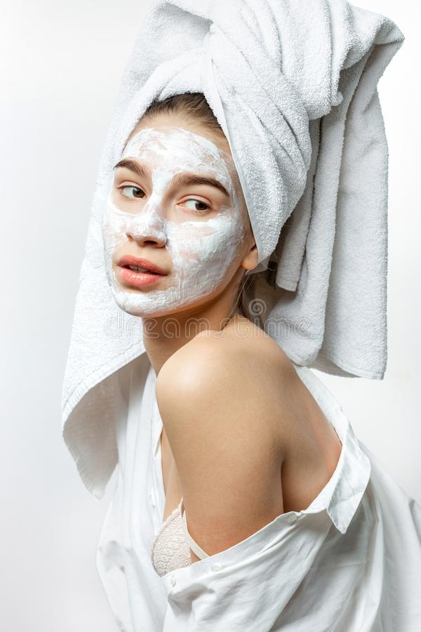 Beautiful young woman dressed in white clothes with a white towel on her hair and cosmetic mask on her face holds her royalty free stock photography
