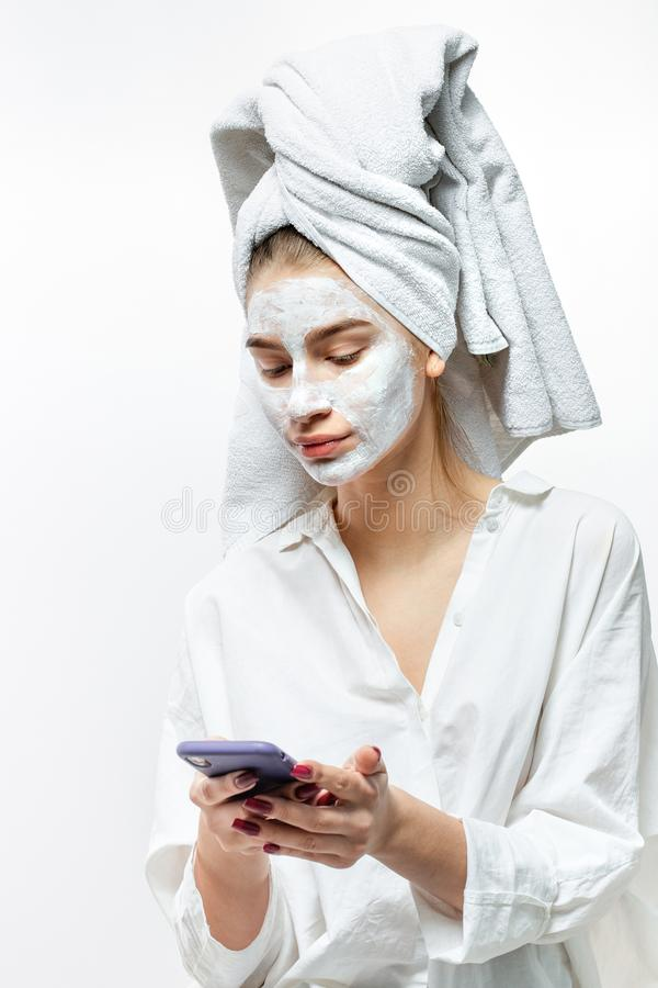 Beautiful young woman dressed in white clothes with a white towel on her hair and cosmetic mask on her face holds mobile royalty free stock image