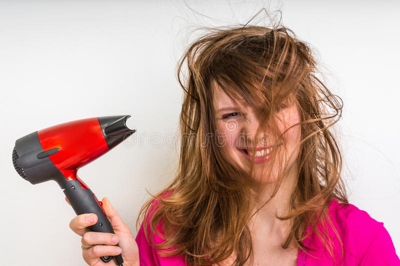 Beautiful young woman dries hair with hair dryer stock image