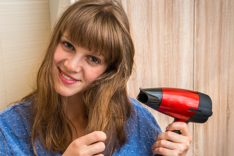 Beautiful young woman dries hair with hair dryer royalty free stock image