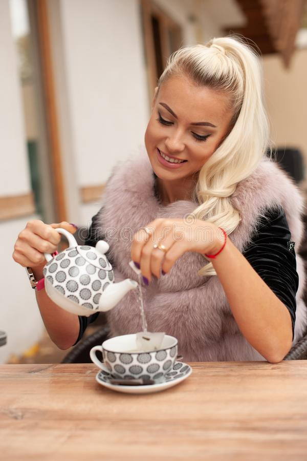 Beautiful young woman drink tea on bar terace in early autumn stock image