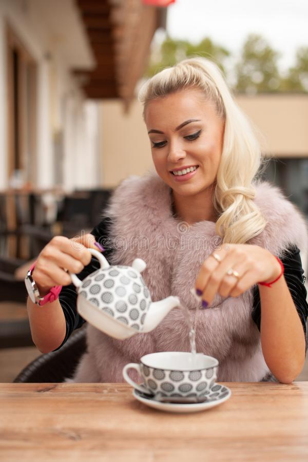 Beautiful young woman drink tea on bar terace in early autumn stock photography