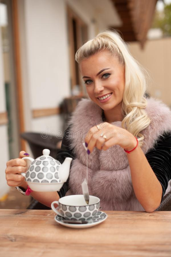 Beautiful young woman drink tea on bar terace in early autumn royalty free stock image