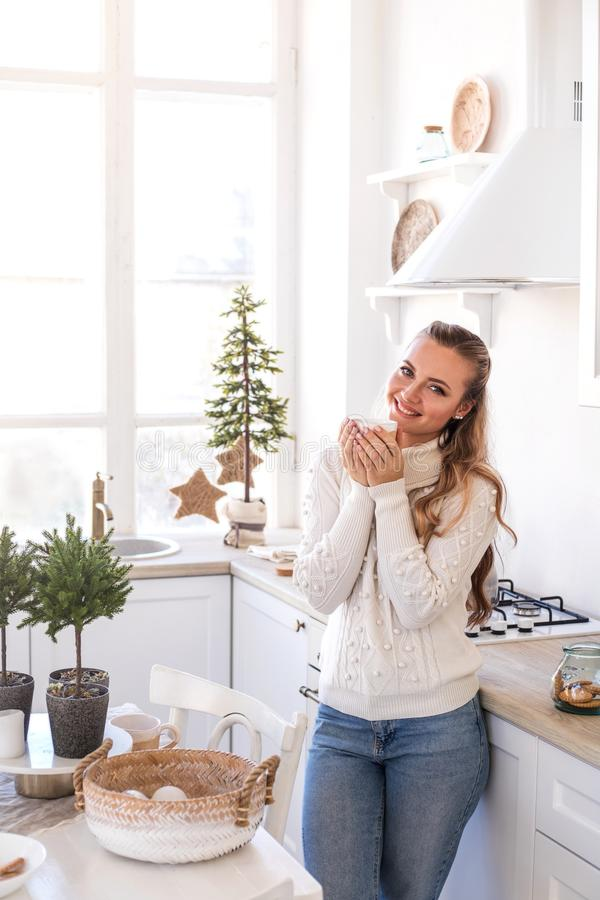 Beautiful young woman drink tea at the festive kitchen. stock photo