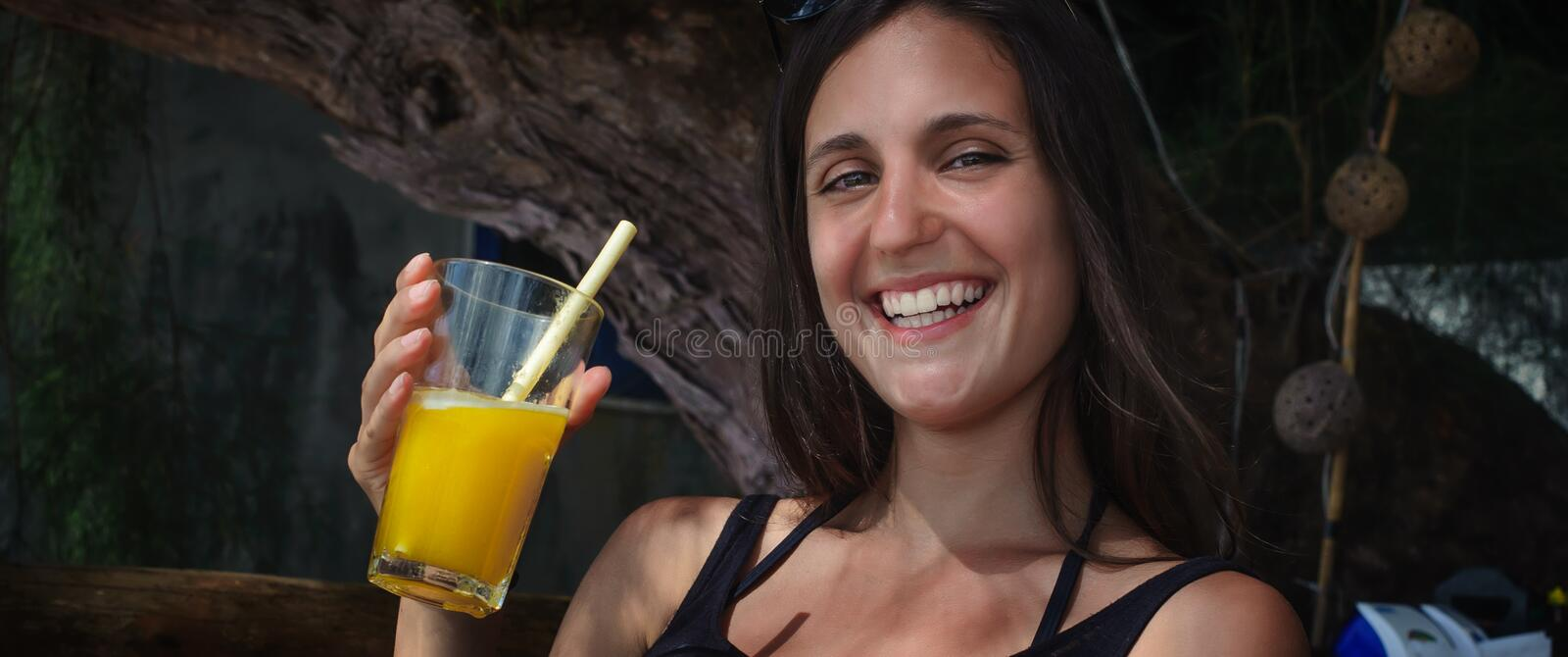 Beautiful young woman drinking fruit cocktail on a tropical beach. Beautiful young woman sitting in bar cafe, drinking fruit cocktail on a tropical beach stock image