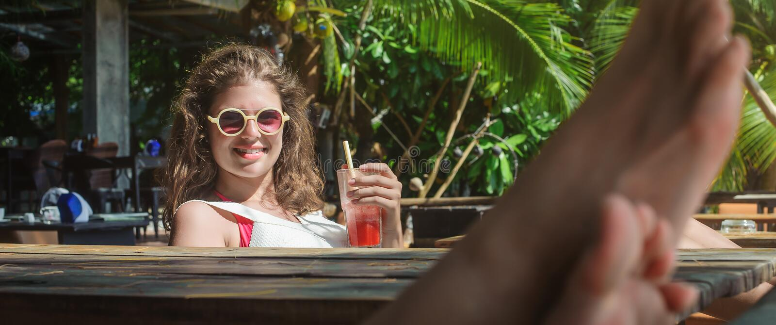 Beautiful young woman drinking fruit cocktail on a tropical beach. Beautiful young women sitting in bar cafe, drinking fruit cocktail on a tropical beach royalty free stock photo
