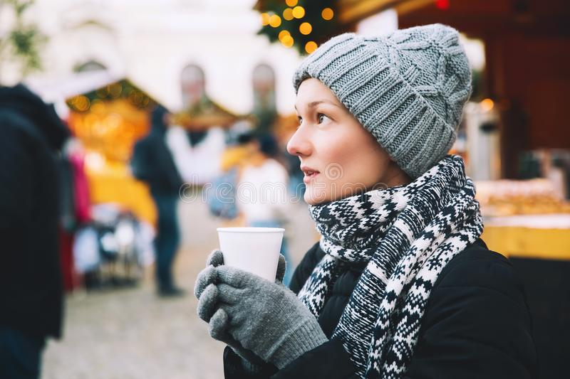 Woman drinking hot tea or mulled wine at Christmas in Europe royalty free stock photos