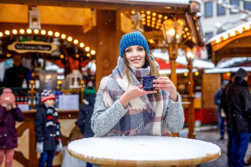 Beautiful young woman drinking hot punch, mulled wine on German Christmas market. Happy girl in winter clothes with royalty free stock photo