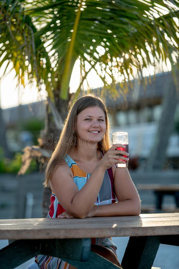 Beautiful young woman drinking juice on beach royalty free stock photo
