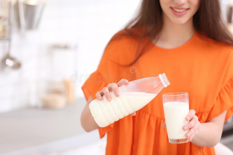Beautiful young woman drinking milk. In kitchen royalty free stock images