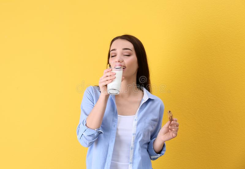 Beautiful young woman drinking milk with cookie. On color background royalty free stock photos