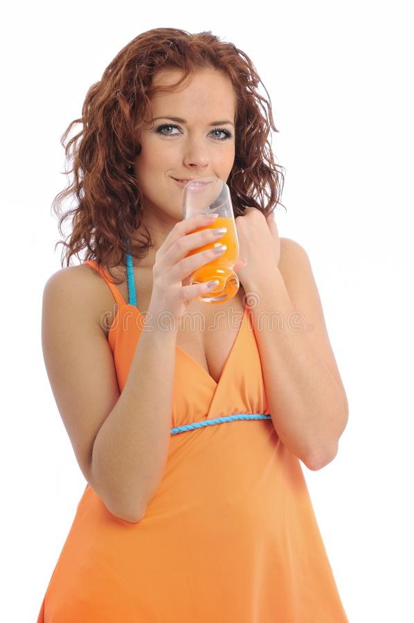 Beautiful young woman drinking orange juice royalty free stock photos