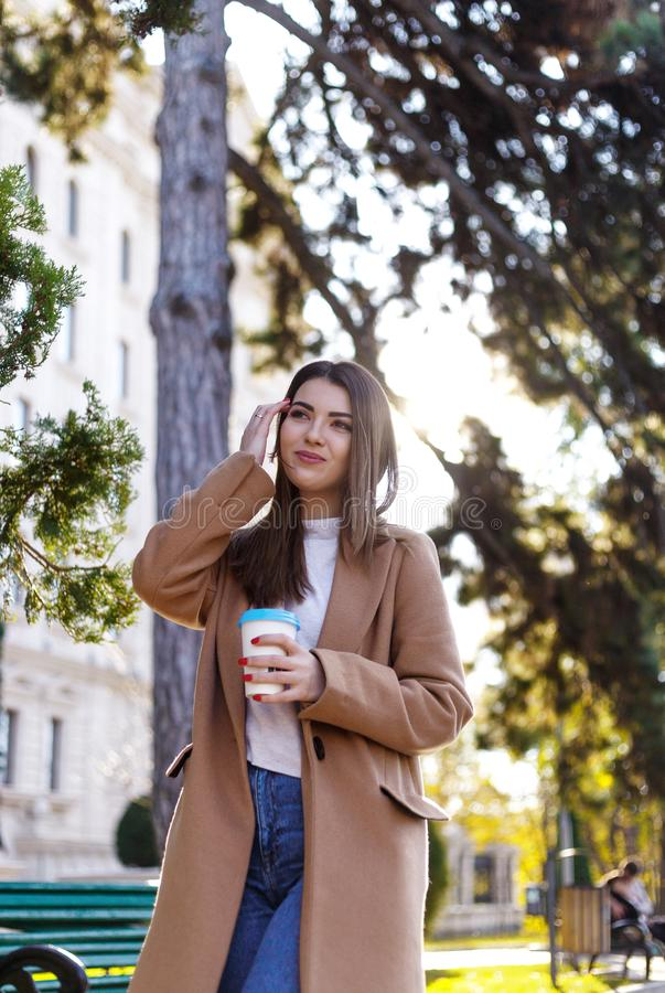 Beautiful young woman drinking takeaway coffee in park in autumn. Pretty girl outdoors in fall with coffee cup smiling. royalty free stock image