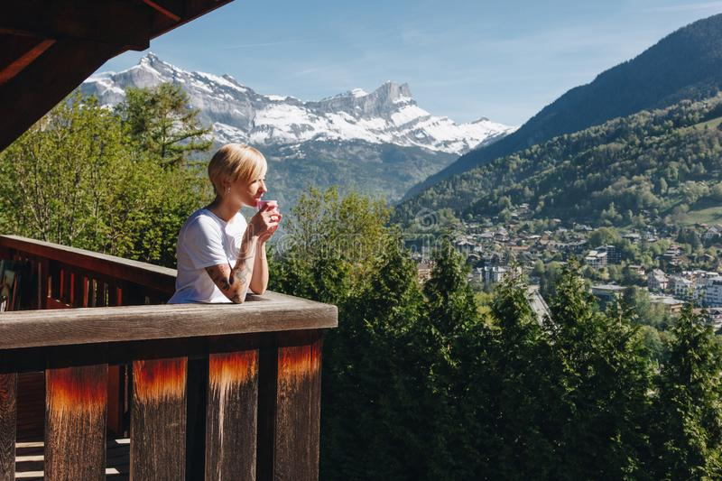 beautiful young woman drinking tea on balcony and looking at majestic mountains mont royalty free stock photos