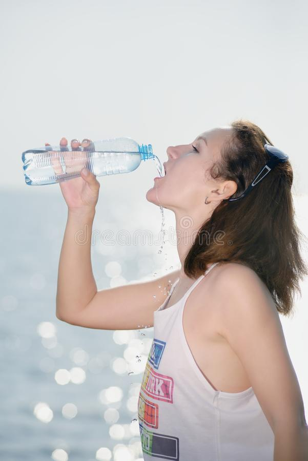 Beautiful young woman drinking water royalty free stock images