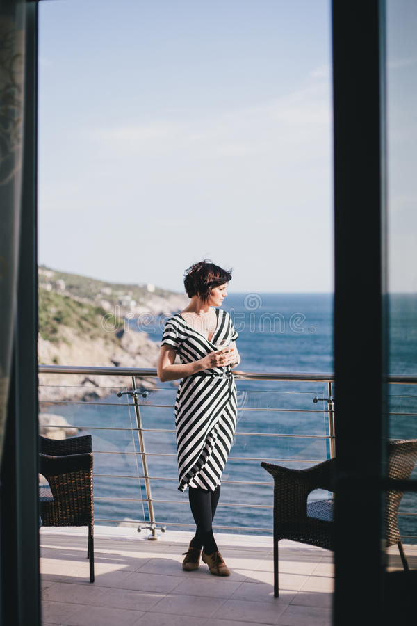Beautiful young woman drinking wine and standing on a balcony with beautiful ocean view. Beautiful young woman wearing black and white dress drinking wine and stock photos