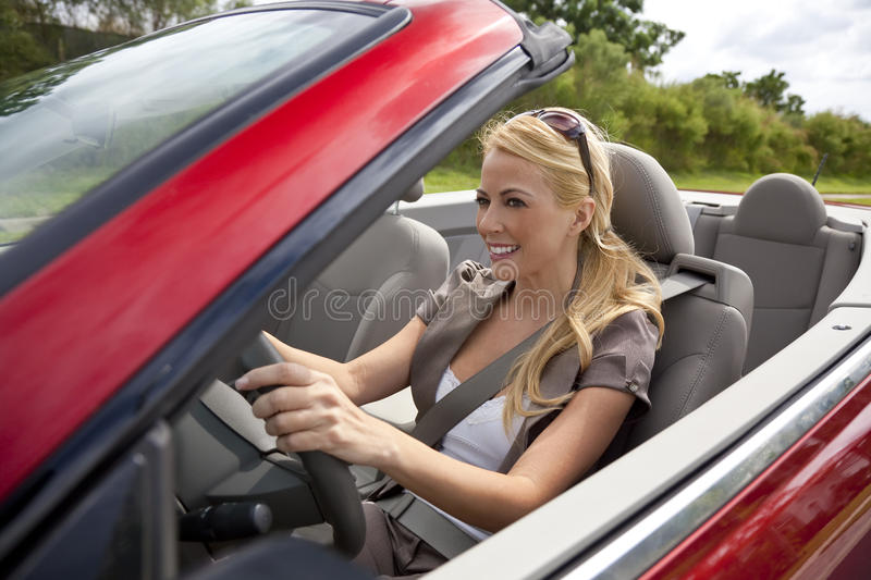 Beautiful Young Woman Driving Convertible Car stock images