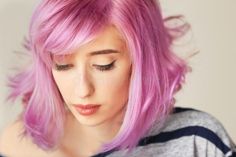 Beautiful young woman with dyed hair on color background. Closeup stock photography