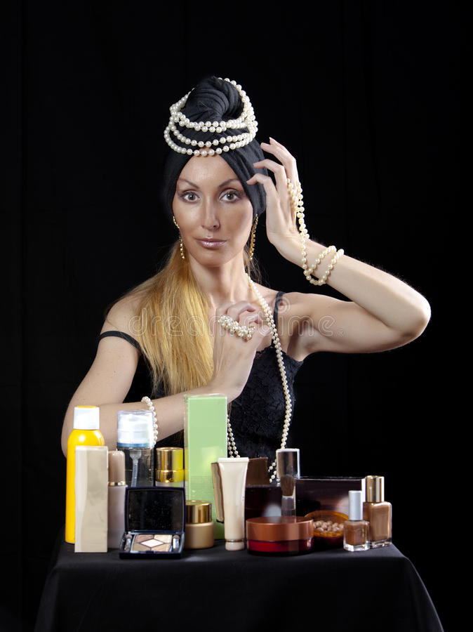 Beautiful young woman in east turban, with pearl beads and a lot of cosmetics on dark background royalty free stock image