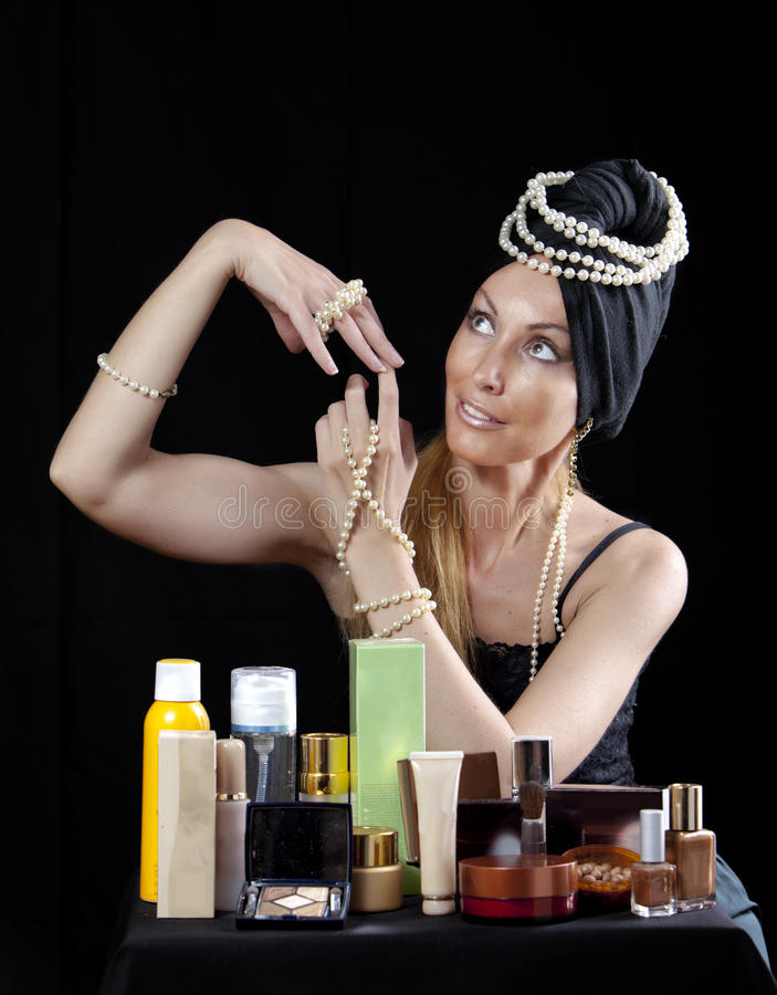 Beautiful young woman in east turban, with pearl beads and a lot of cosmetics on dark background stock image