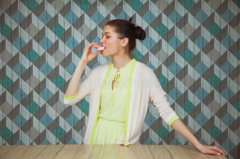 Beautiful young woman eat dessert on a blue background stock image