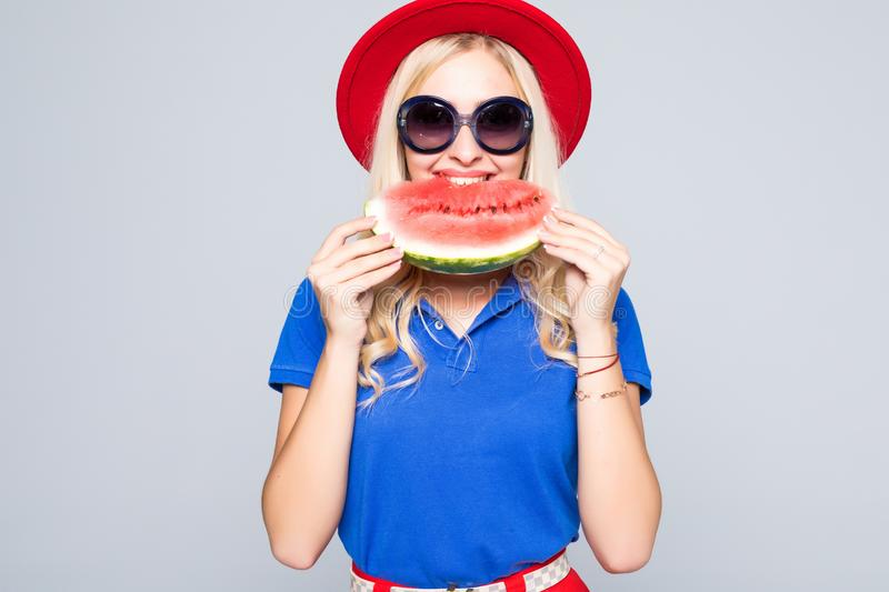 Beautiful young woman eat juicy watermelon over gray stock photography