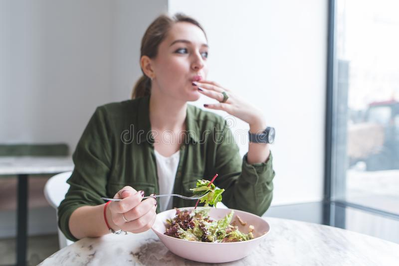 Beautiful young woman eating salad in a restaurant and looking in the window. Focus on a salad plate royalty free stock image