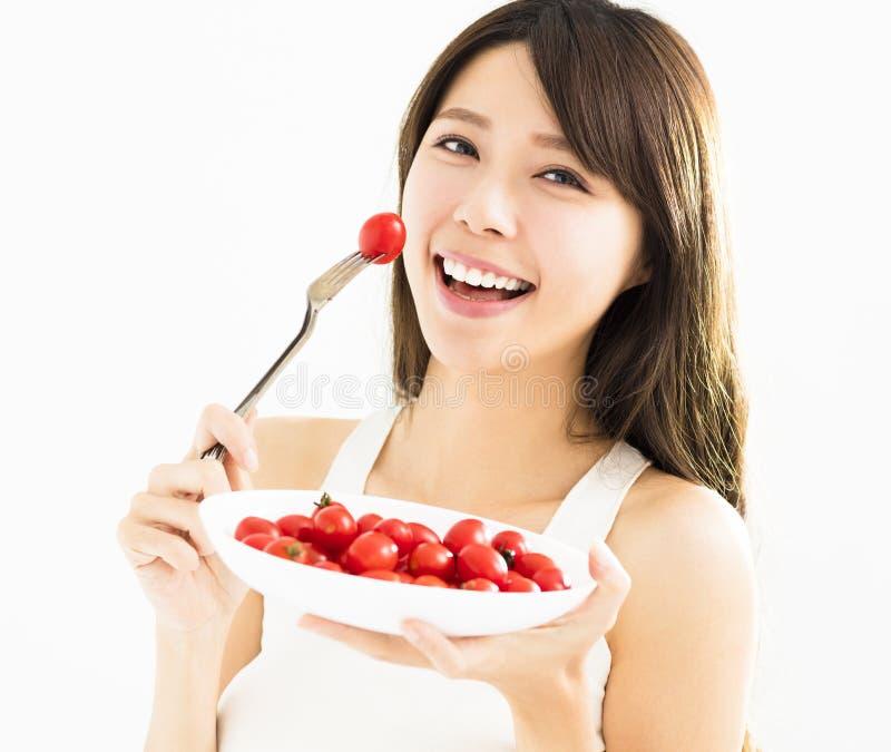 Beautiful Young Woman Eating Tomatoes. Asian beautiful Young Woman Eating Tomatoes royalty free stock photo