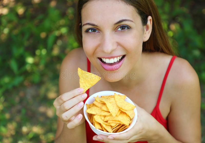 Beautiful young woman eating tortilla chips outdoor royalty free stock image
