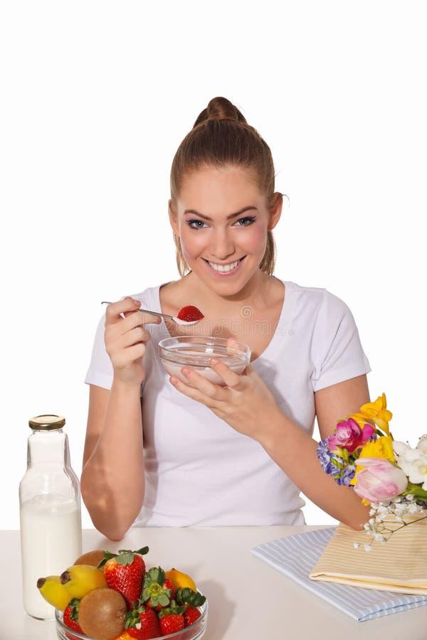 Beautiful young woman eating yogurt with strawberry