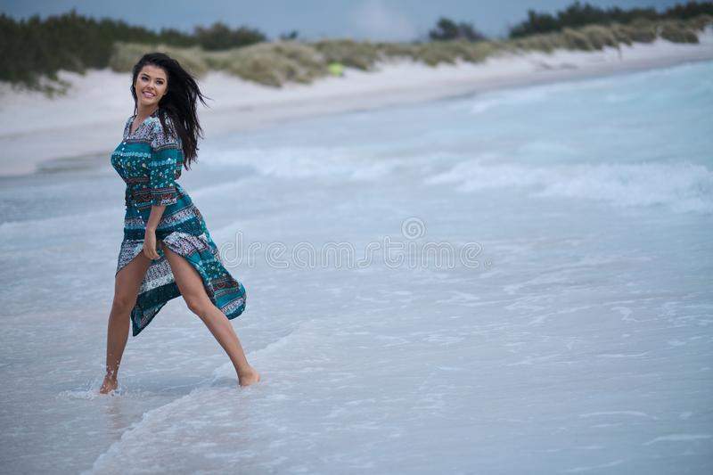 Beautiful young woman in elegant dress on the beach stock photo